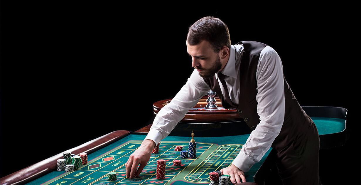 croupier che muove delle carte sul tavolo verde